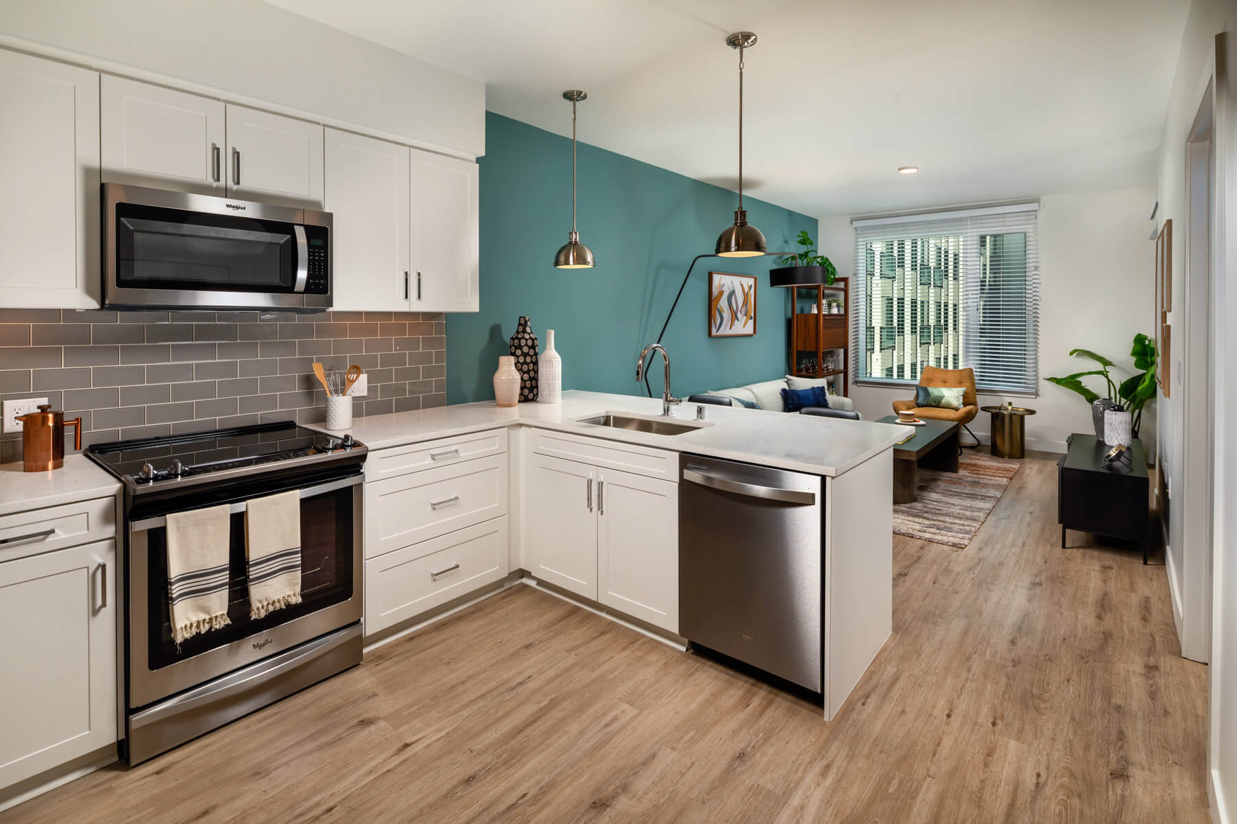 Apartments in DTLA for Rent - Sleek Kitchen With White Cabinets, Quartz Countertops, Stainless Steel Appliances, and Gray Subway Tile