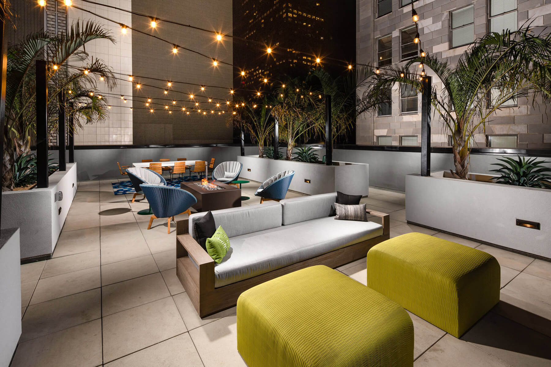 Apartments for Rent in Downtown Los Angeles CA - Beautiful Rooftop Lounge With String Lighting, Firepit Surrounded by Plush Outdoor Seating, and Gorgeous View of Los Angeles Skyline.